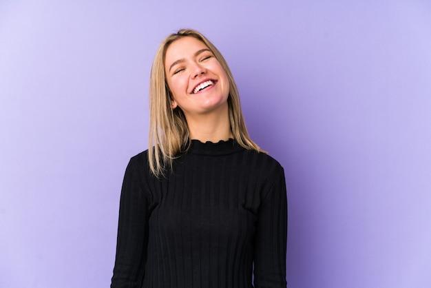 Jonge blonde blanke vrouw geïsoleerd ontspannen en gelukkig lachen, nek gestrekt met tanden.