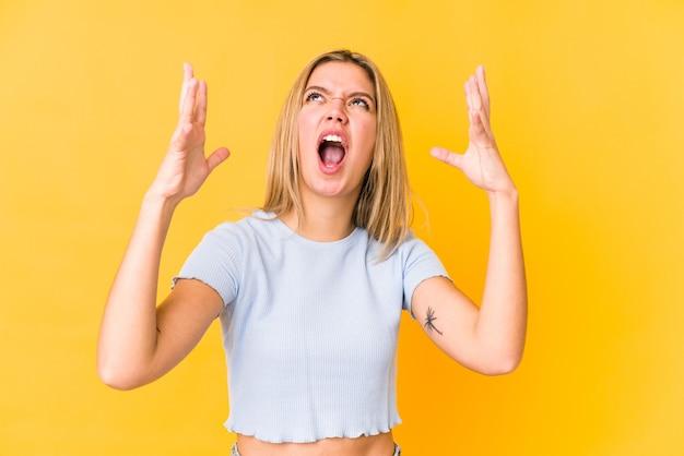 Jonge blonde blanke vrouw geïsoleerd op geel schreeuwen naar de hemel, gefrustreerd opzoeken.