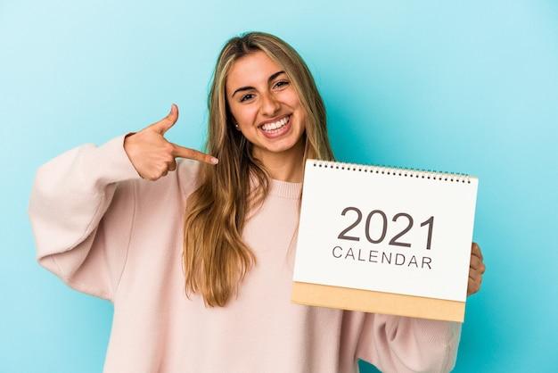 Jonge blonde blanke vrouw holing een kalender geïsoleerde persoon met de hand wijzend naar een shirt kopie ruimte, trots en zelfverzekerd