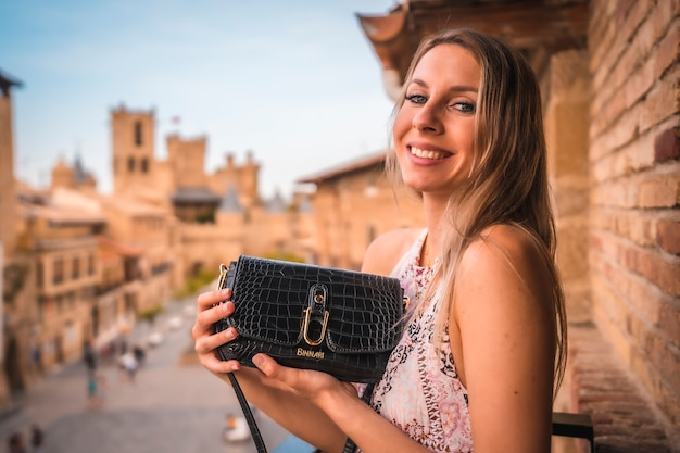 Jonge blonde blanke vrouw in een lange roze jurk genieten van een prachtig landelijk hotel in de middeleeuwse stad