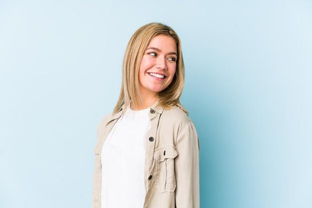 Jonge blonde blanke vrouw kijkt opzij lachend, vrolijk en aangenaam.
