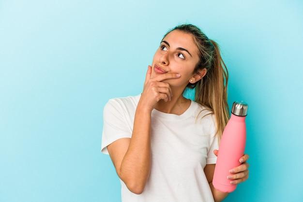 Jonge blonde blanke vrouw met een thermoskan geïsoleerd op een blauwe achtergrond opzij kijkt met twijfelachtige en sceptische uitdrukking.