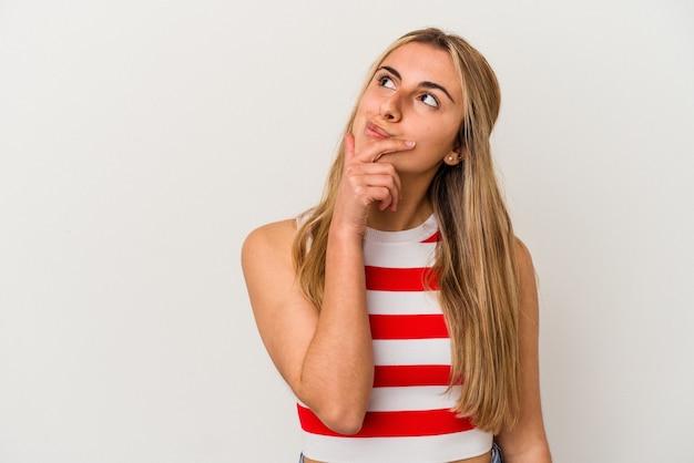 Jonge blonde blanke vrouw op witte achtergrond geïsoleerd zijwaarts op zoek met twijfelachtige en sceptische uitdrukking.