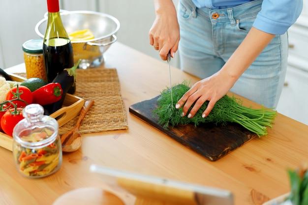 Jonge blonde blanke vrouw snijden groenten voor salade in haar keuken