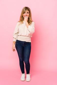 Jonge blonde blanke vrouw staande op roze nagels bijten, nerveus en erg angstig.