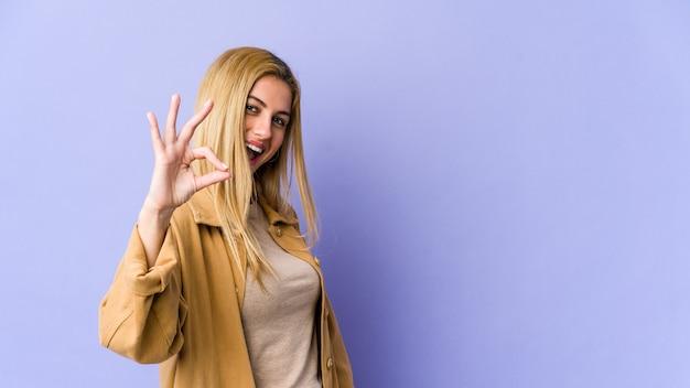 Jonge blonde blanke vrouw vrolijk en zelfverzekerd met ok gebaar.