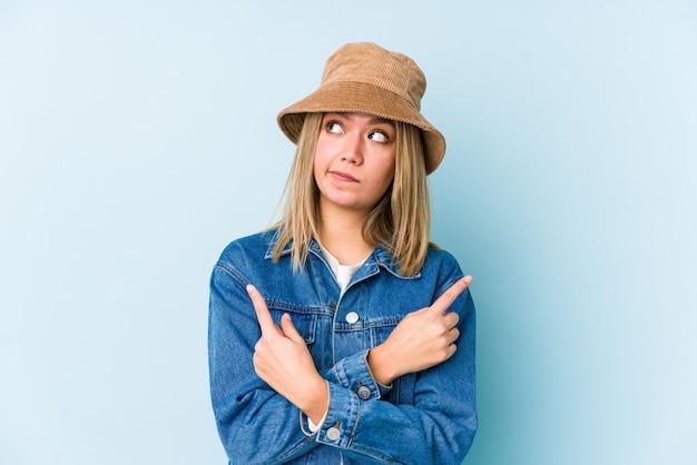 Jonge blonde blanke vrouw wijst zijwaarts en probeert te kiezen tussen twee opties.