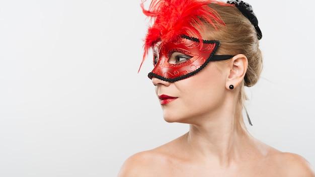 Jonge blonde dame in masker met rode veren