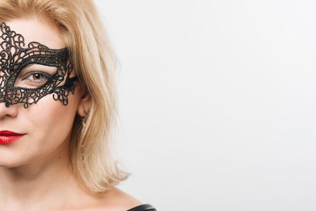 Jonge blonde dame in masker