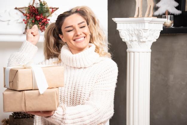 Jonge blonde dame met geschenken in de buurt van open haard.