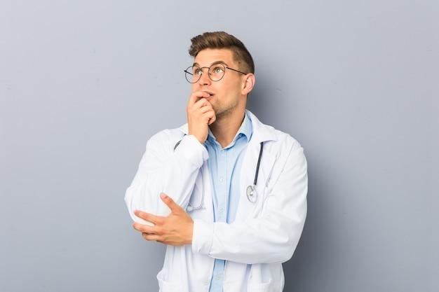 Jonge blonde dokter man ontspannen denken aan iets kijken naar een kopie ruimte.