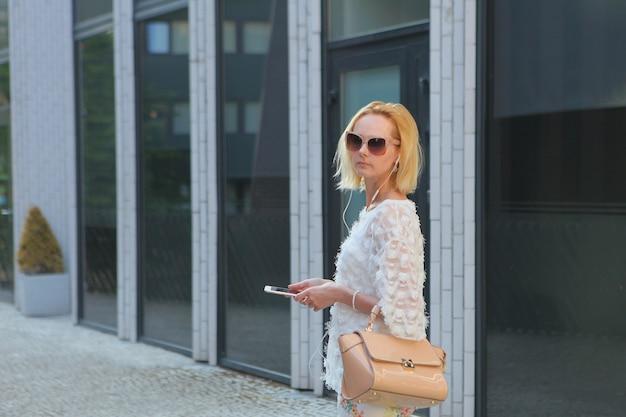 Jonge blonde europese vrouw die een smartphone gebruikt terwijl ze in het winkelgebied van een stad staat, met huisramen op moderne achtergrond. zonnebril en handtas dragen.