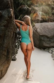 Jonge blonde europese vrouw in bikini zwembroek op strand tegen stenen rotsen staat achteruit