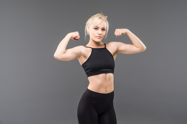 Jonge blonde fit sportieve meisje vrouw in zwarte sportkleding demostrate haar sterke gespierde lichaam uitrekken