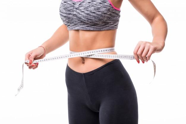 Jonge blonde fitness vrouw haar lichaam meten met liniaal gekleed in fasion sportkleding afvallen concept
