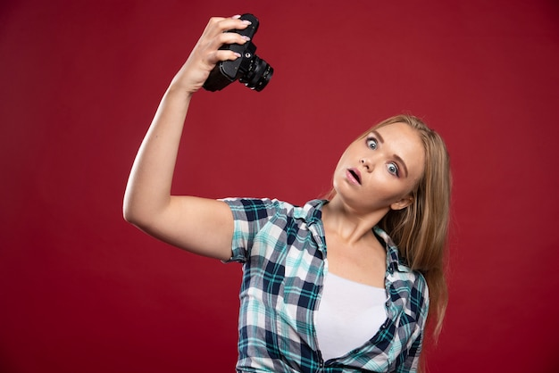 Jonge blonde foto met een professionele camera en neemt haar selfie in vreemde posities.
