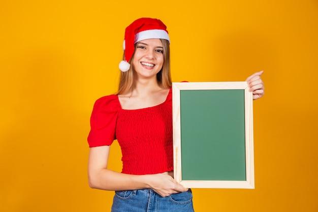 Jonge blonde gekleed voor kerstmis met een bordje. kerstmis