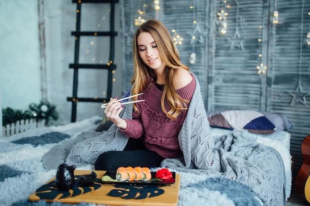 Jonge blonde, gekrulde vrouw die thuis sushi eet