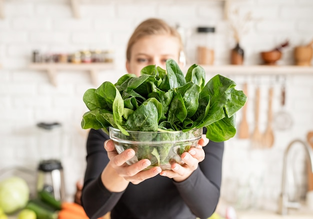 Jonge blonde glimlachende vrouw die een kom verse spinazie in de keuken houdt