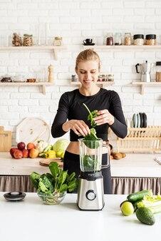 Jonge blonde glimlachende vrouw die groene smoothie thuis keuken maakt