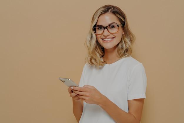 Jonge blonde glimlachende zakenvrouw in vrijetijdskleding en bril met behulp van mobiele telefoon, het controleren van e-mails op smartphone terwijl ze tijd binnenshuis doorbrengen, kijkend naar camera met positieve gezichtsuitdrukking