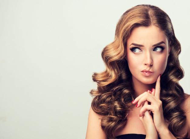 Jonge blonde haired model met een verbaasde gezichtsuitdrukking twijfels over het gezicht van aantrekkelijke vrouw goed verzorgd blond haar felrode make-up en manicure afbeelding in pin up-stijl