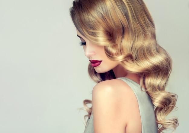 Jonge, blonde haired vrouw met elegant, omvangrijk avondkapsel. profiel van een vrouw omlijst door glanzende krullen van bonde haar. kappers kunst, haarverzorging en make-up.