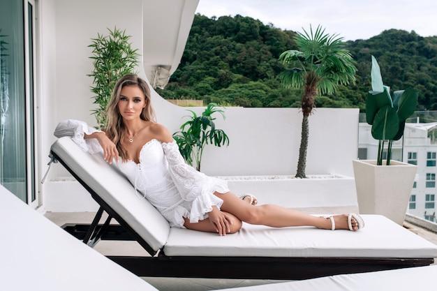 Jonge blonde in een witte jurk poseren kijken naar de camera liggend op een ligstoel. reis- en vakantieconcept.