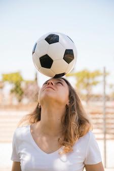 Jonge blonde in evenwicht brengende voetbalbal op hoofd in stadion