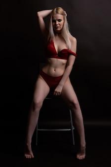 Jonge blonde in ondergoed maakt haar haren recht terwijl ze op een stoel zit