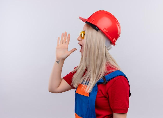 Jonge blonde ingenieur bouwer meisje in uniform dragen veiligheidsbril schreeuwen tegen iemand met hand in de buurt van mond staande in profiel te bekijken op geïsoleerde witte muur met kopie ruimte