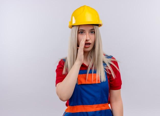 Jonge blonde ingenieur bouwer meisje in uniform hand zetten in de buurt van mond fluisteren op geïsoleerde witte muur met kopie ruimte