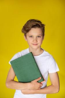 Jonge blonde jongen met groen boek op gele muur