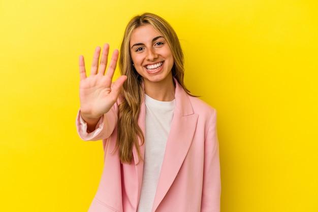 Jonge blonde kaukasische die vrouw op gele achtergrond wordt geïsoleerd die vrolijk glimlachen toont nummer vijf met vingers.