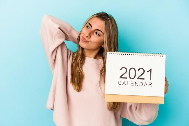 Jonge blonde kaukasische vrouw die een kalender maakt die geïsoleerd is, achterhoofd aanraakt, denkt en een keuze maakt.