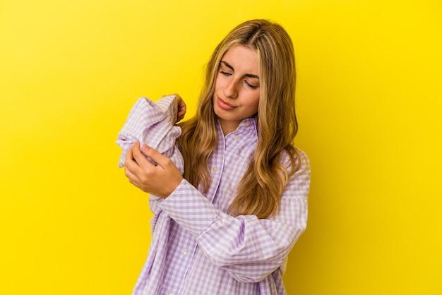 Jonge blonde kaukasische vrouw die op gele achtergrond wordt geïsoleerd die elleboog masseert, die lijdt na een slechte beweging.