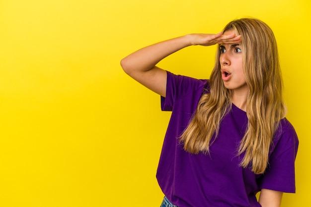 Jonge blonde kaukasische vrouw die op gele achtergrond wordt geïsoleerd die ver weg kijkt die hand op voorhoofd houdt.