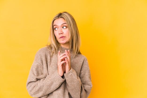 Jonge blonde kaukasische vrouw die op gele ruimte wordt geïsoleerd die plan in mening verzint, een idee opzet.