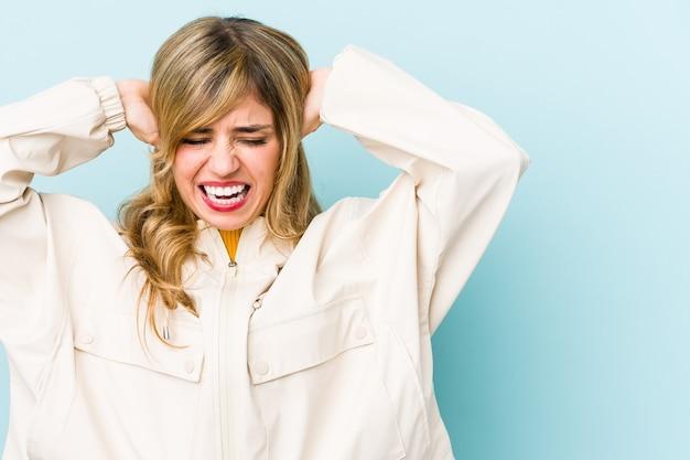 Jonge blonde kaukasische vrouw die oren behandelt met handen die niet te hard geluid proberen te horen.