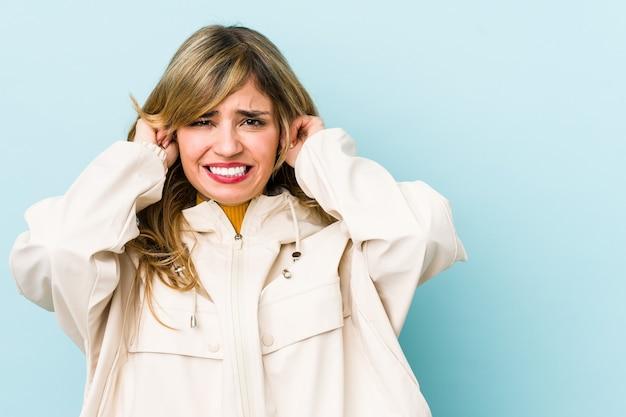 Jonge blonde kaukasische vrouw die oren behandelt met handen.
