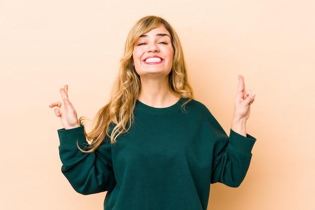 Jonge blonde kaukasische vrouw die vingers voor het hebben van geluk kruist