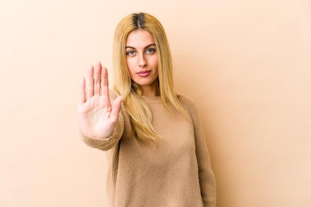 Jonge blonde kaukasische vrouw die zich met uitgestrekte hand bevindt die stopbord toont, dat u verhindert.