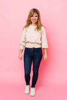 Jonge blonde kaukasische vrouw die zich over een roze muur bevindt die zeer boos en agressief gilt.