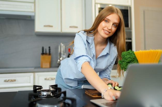 Jonge blonde kaukasische vrouw met lang haar die laptop in een keuken met behulp van