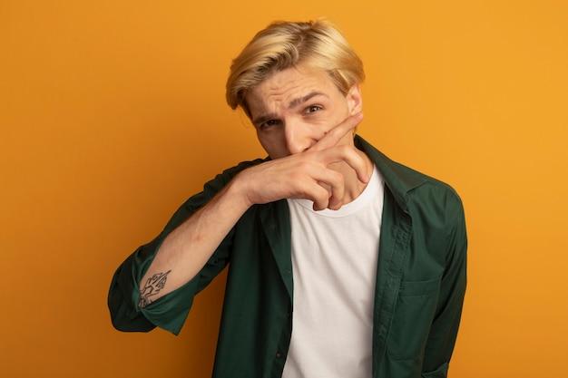 Jonge blonde kerel die groene t-shirt draagt die neus met hand afveegt