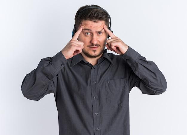 Jonge blonde knappe man met een headset trekt zijn wenkbrauwen op met handen die een denkgebaar doen terwijl hij naar de camera kijkt