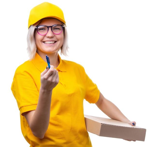 Jonge blonde koerier met bril en een geel t-shirt met doos en pen in haar handen op wit