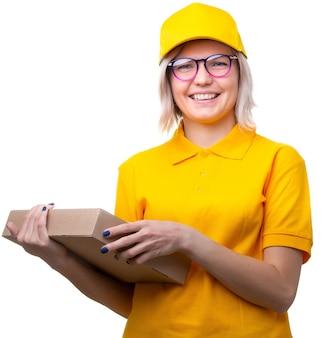 Jonge blonde koerier met bril en geel t-shirt met doos in haar handen op wit