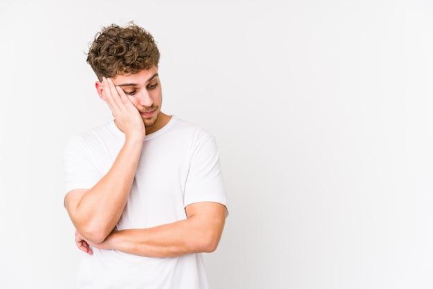 Jonge blonde krullende blanke man geïsoleerd die verdrietig en peinzend voelt, kijkend naar kopie ruimte.