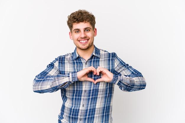 Jonge blonde krullende haar kaukasische mens die en een hartvorm met handen glimlacht toont.
